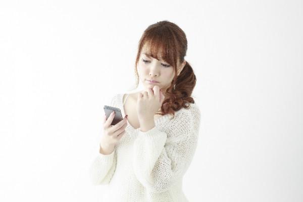 スマホを見て悩む女性