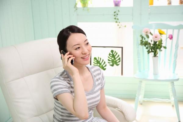 スマートフォンで電話をする笑顔の女性